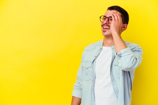 Giovane uomo freddo isolato sulla parete gialla che ride emozione felice, spensierata, naturale