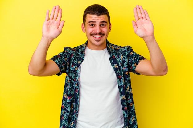 Giovane uomo freddo isolato sulla parete gialla che riceve una piacevole sorpresa, eccitato e alzando le mani