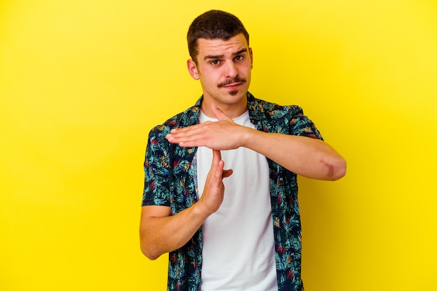 Giovane uomo freddo isolato sulla parete gialla che mostra un gesto di timeout