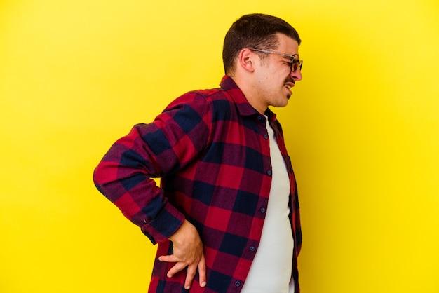 Giovane uomo freddo isolato sulla parete gialla che soffre di mal di schiena