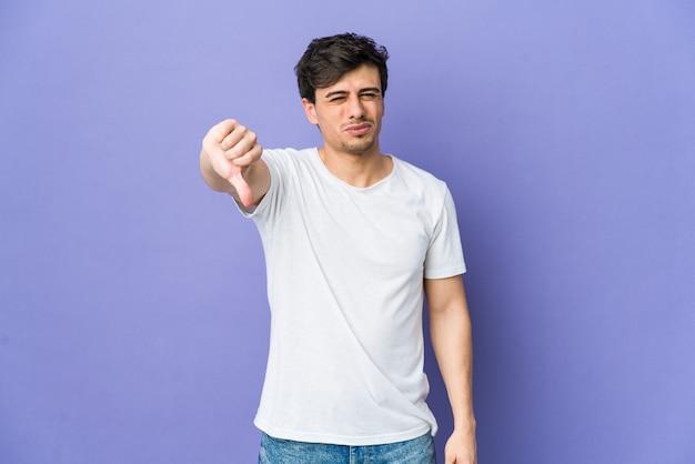Giovane uomo freddo che mostra il pollice verso il basso, concetto di delusione