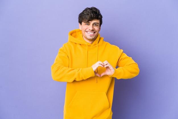 Giovane uomo freddo che sorride e che mostra una forma del cuore con le mani.