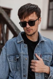 Il giovane uomo freddo raddrizza la giacca blu alla moda del denim. attraente ragazzo urbano hipster in occhiali da sole alla moda in eleganti abiti primaverili in posa in città vicino a un edificio d'epoca. stile di strada. abbigliamento da uomo