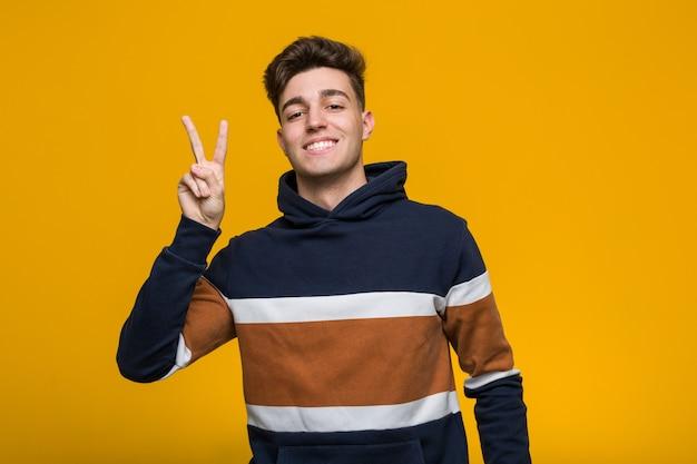 Giovane uomo freddo che indossa una felpa con cappuccio gioiosa e spensierata che mostra un simbolo di pace con le dita.