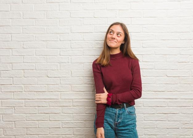 Giovane donna fredda su un muro di mattoni sognando di raggiungere obiettivi e scopi