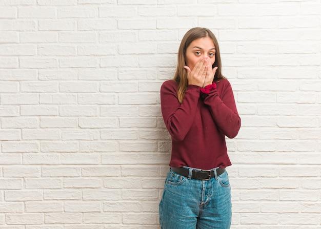 Giovane donna fredda su un muro di mattoni sorpreso e scioccato