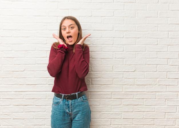 Giovane donna fredda sopra un muro di mattoni sorpreso e scioccato