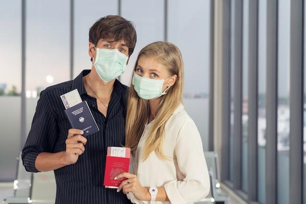 Giovane coppia in aeroporto indossando maschere