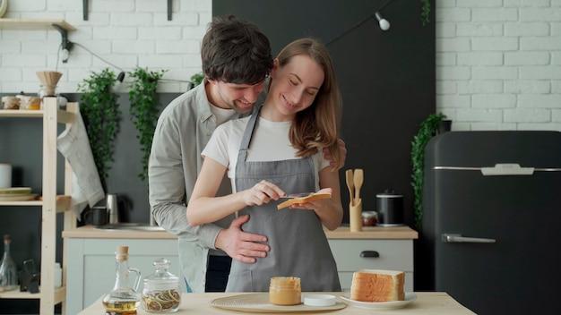 Giovani coppie che applicano burro di arachidi sul pane al mattino