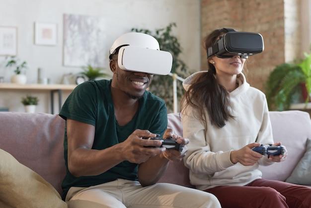 La giovane coppia è felice di giocare ai videogiochi che indossano occhiali virtuali nell'appartamento