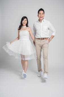 Sposo e sposa asiatici delle giovani coppie in vestito da sposa casuale che camminano e che si divertono