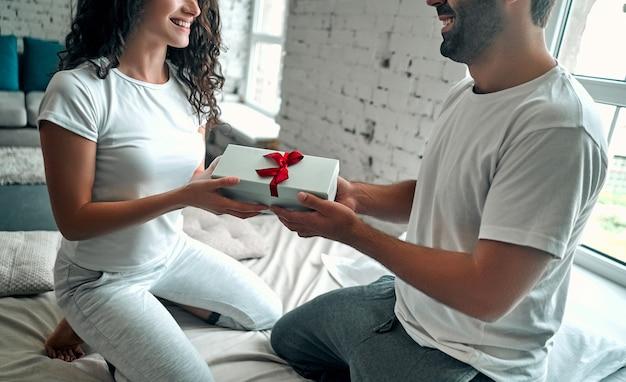 Giovane coppia a letto. un uomo attraente sta dando il regalo alla sua ragazza felice, il romanticismo in una relazione