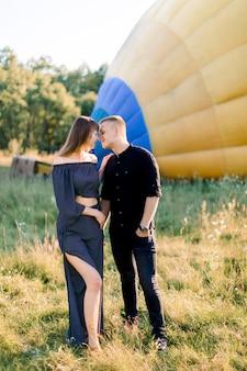 Coppia giovane in abiti neri, abbracciando e tenendo le mani, mentre in piedi nel campo estivo di fronte a una mongolfiera colorata, preparandosi per il volo