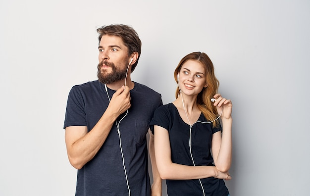 Giovane coppia in magliette nere con le cuffie che ascolta lo stile di vita di tecnologia musicale