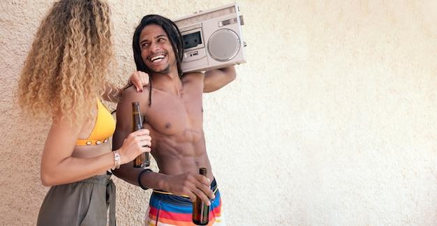 Giovane coppia di donna bionda caucasica e ragazzo afro-americano con una birra alla festa in piscina