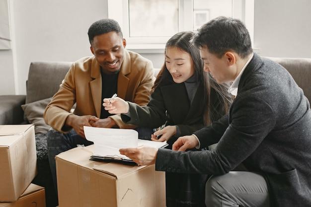 Giovani coppie che comprano una nuova casa. donna asiatica e uomo africano. firma dei documenti nella nuova casa.