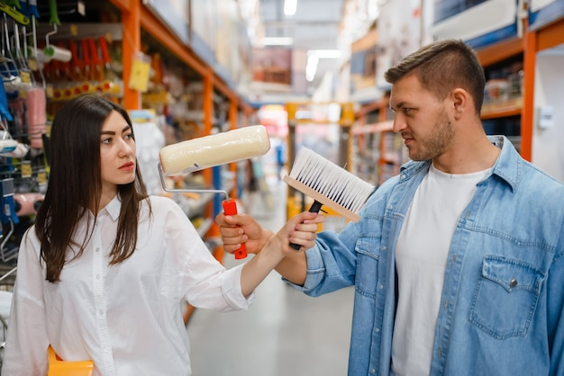 Coppia giovane acquistare la piastra per la pittura e il pennello nel negozio di ferramenta. i clienti maschi e femmine guardano le merci nel negozio di bricolage