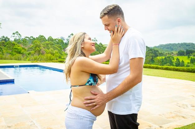Coppia giovane in piscina. uomo che accarezza la pancia della donna incinta.