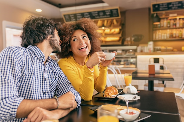 Giovane coppia al caffè, il ragazzo le sta bisbigliando e lei è sorpresa.