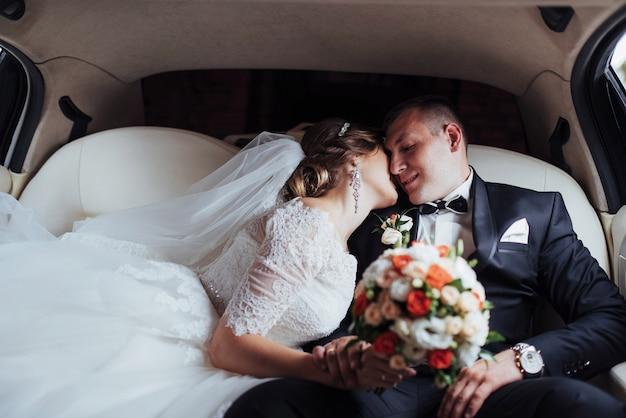 Giovani coppie in un'automobile nel giorno delle nozze