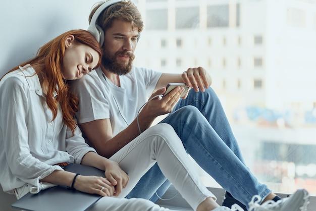 Una giovane coppia che chiacchiera vicino alla finestra romanticismo gioia tecnologia