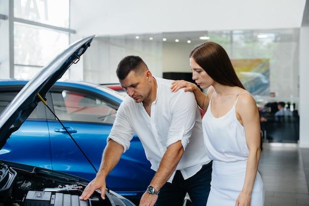 Una giovane coppia sceglie una nuova auto presso la concessionaria e consulta un rappresentante della concessionaria. auto usate in vendita. realizzazione del sogno.