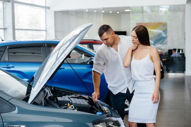 Una giovane coppia sceglie un'auto nuova presso la concessionaria e si consulta con un rappresentante della concessionaria. auto usate in vendita. realizzazione del sogno.
