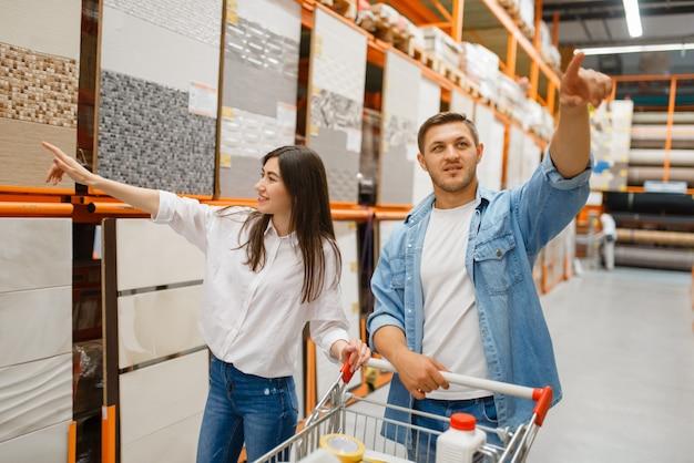 Coppia giovane scegliendo piastrelle di ceramica nel negozio di ferramenta. i clienti maschi e femmine guardano le merci nel negozio di bricolage