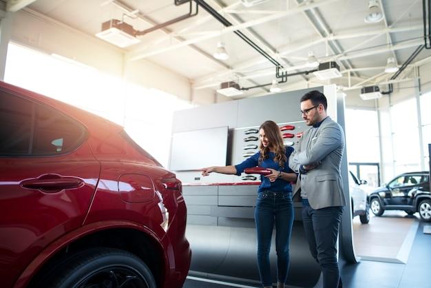 Giovani coppie che scelgono il colore preferito per la loro auto nuova di zecca presso lo showroom del concessionario auto.