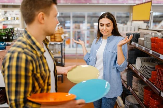Coppia giovane scegliendo i piatti nel negozio di casalinghi. uomo e donna che acquistano beni per la casa nel mercato, famiglia nel negozio di articoli da cucina