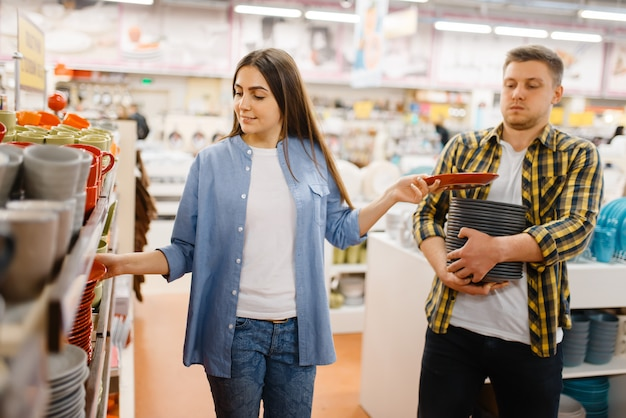 Coppia giovane scegliendo i piatti nel negozio di casalinghi