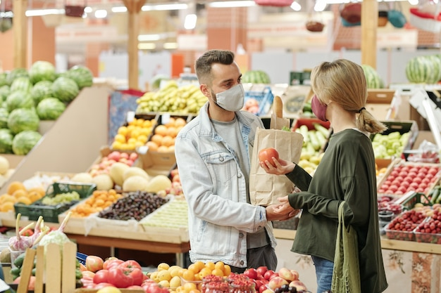 Giovane coppia in maschere di stoffa in piedi al bancone e acquisto di alimenti biologici al mercato: ragazza che sceglie i pomodori