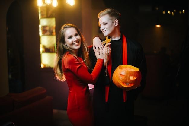 Giovane coppia di studenti universitari travestiti da prete e strega su una festa di halloween. giovane coppia in posa con una zucca in mano e guardando la telecamera