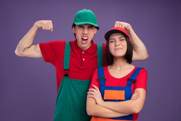 Giovani coppie in uniforme dell'operaio edile e berretto ragazzo aggressivo in piedi dietro la ragazza che fa forte gesto urlando ragazza soddisfatta in piedi con la postura chiusa