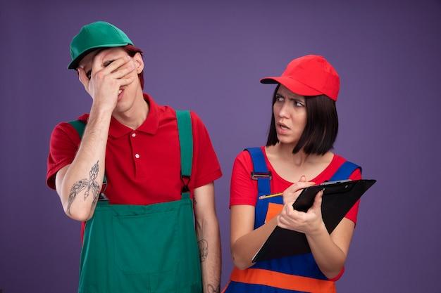 Giovane coppia in uniforme da operaio edile e berretto ragazza con matita e appunti ragazzo stanco che tiene la mano sul viso ragazza accigliata che lo guarda