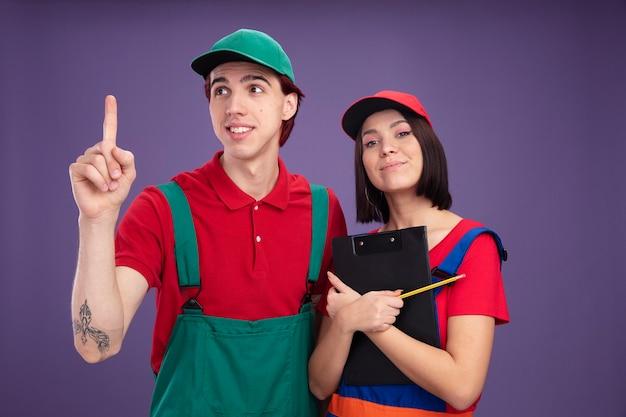 Giovani coppie in uniforme dell'operaio edile e ragazza del berretto che tiene matita e ragazzo sorridente della lavagna per appunti che esamina il lato che indica in su la ragazza soddisfatta che abbraccia appunti isolati