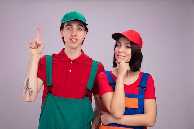 Giovane coppia in uniforme da operaio edile e cappello impressionato da un ragazzo che indica una ragazza premurosa che tiene la mano sul mento entrambi