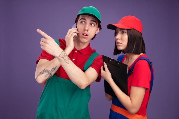Giovane coppia in uniforme da operaio edile e berretto che guarda di lato un ragazzo interessato che parla al telefono puntando a lato una ragazza concentrata che tiene appunti