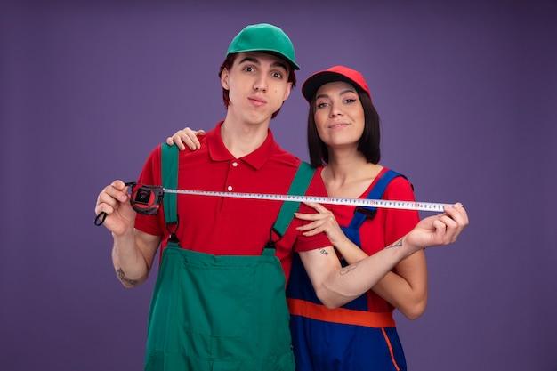 Giovane coppia in uniforme da muratore e berretto soddisfatto ragazza in piedi dietro il ragazzo che tiene le mani sulla spalla e il braccio ha impressionato il ragazzo che mostra il metro a nastro