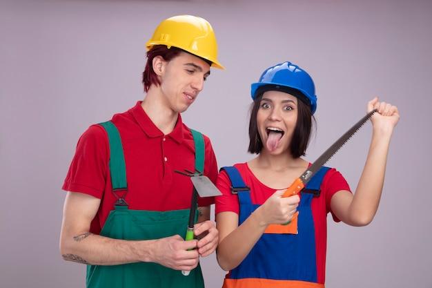 Giovane coppia in uniforme da operaio edile e casco di sicurezza ragazzo sorridente che tiene la zappa rastrello guardando la ragazza giocosa che mostra la sega a mano e la lingua