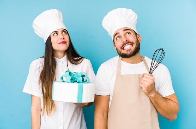 Giovani coppie che cucinano una torta insieme isolate sognando di raggiungere obiettivi e scopi