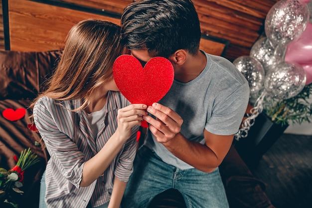 La giovane coppia si copre il viso con un cuore, si bacia e festeggia san valentino.