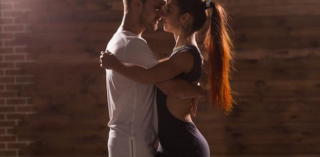 Giovani coppie che ballano musica latina: bachata, merengue, salsa. due pose di eleganza sulla stanza bianca.