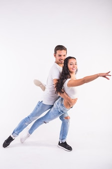 Giovani coppie che ballano bachata di ballo sociale, merengue, salsa, kizomba. due pose di eleganza sulla stanza bianca