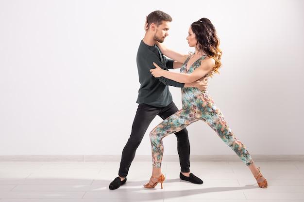 Giovani coppie che ballano bachata di ballo latino sociale, merengue, salsa. due pose di eleganza sulla parete bianca.