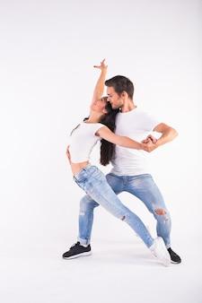 Giovani coppie che ballano bachata di ballo latino sociale, merengue, salsa. due pose di eleganza su bianco