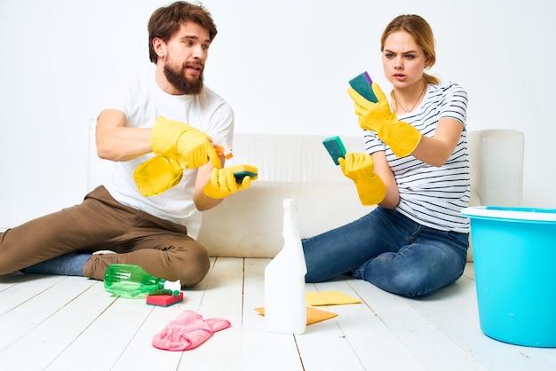 Giovane coppia detersivo lavare il pavimento lavorando insieme