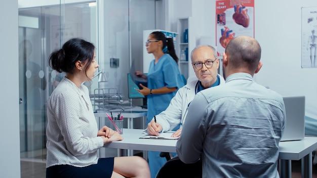 Giovani coppie all'appuntamento del medico che parlano e che condividono i loro problemi di infertilità. specialista in pianificazione familiare. persone nel moderno ospedale o clinica privata, problemi di medicina e assistenza sanitaria.
