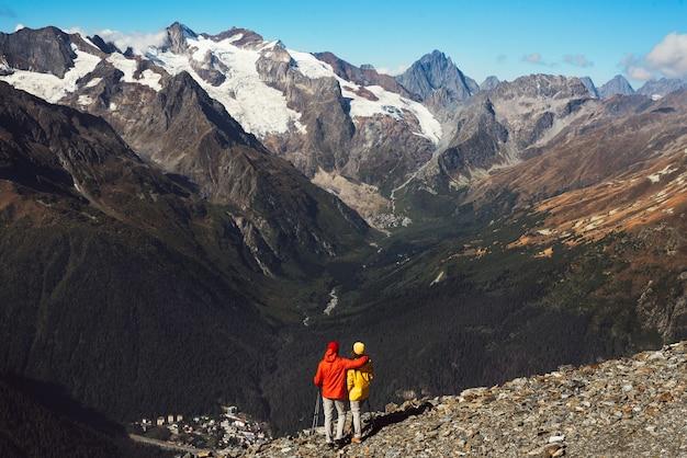 Coppia giovane facendo nordic walking in montagna, vista posteriore. una coppia attiva è impegnata in escursionismo. una giovane coppia è impegnata nel monitoraggio. trekking e nordic walking. escursionismo. copia spazio