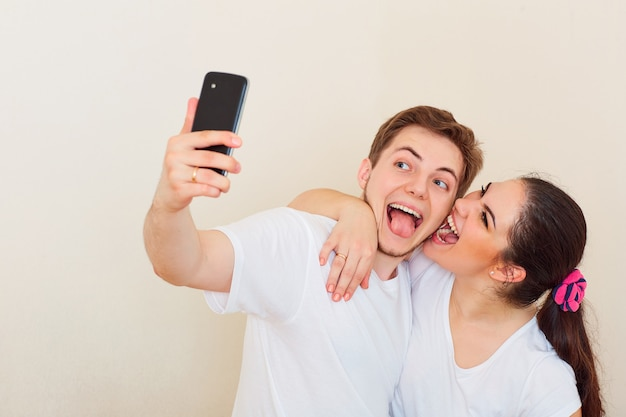 Giovane coppia che fa selfie con il telefono sorridendo ridendo e scherzando